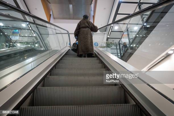 An elderly woman is seen standing on an escalator in the Focus Park shopping mall on 8 May 2017