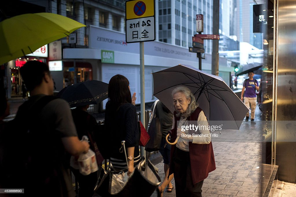 An elderly woman is seen through a showcase as she walks during a rainstorm on August 20, 2014 in Hong Kong, Hong Kong. A government-commissioned study headed by University of Hong Kong academic Nelson Chow Wing-sun proposed to fund HK $3,000 a month pension for every Hongkonger over 65, rich or poor, without a means test. The pension should be funded partly by contributions ranging from 1 to 2.5 per cent of employees' salaries, paid by employers and workers. One in three old people in Hong Kong lives below estimated poverty line some of them struggling to make a living collecting cardboard boxes and plastic bottles on the street.