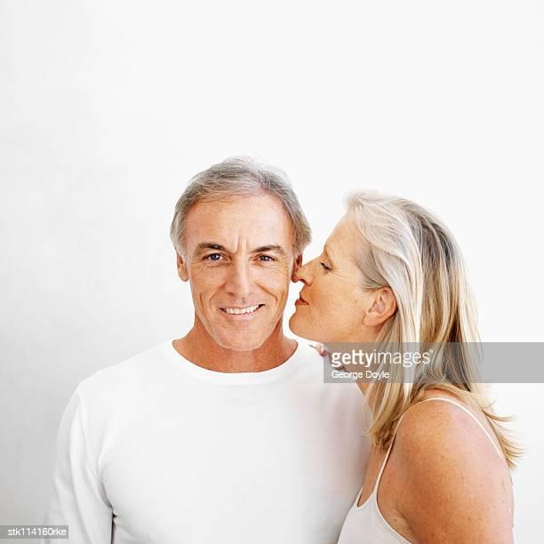 An elderly woman kissing an elderly man on the cheek