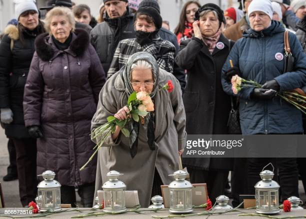 An elderly woman lays flowers at the portraits of the NordOst musical hostage drama victims at the Dubrovka Theatre in Moscow on October 26 during a...
