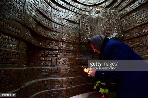 An elderly woman lights a candle at the monument commemorating the Soviet victims of the war in Afghanistan in Minsk on February 15 2016 Belarus on...