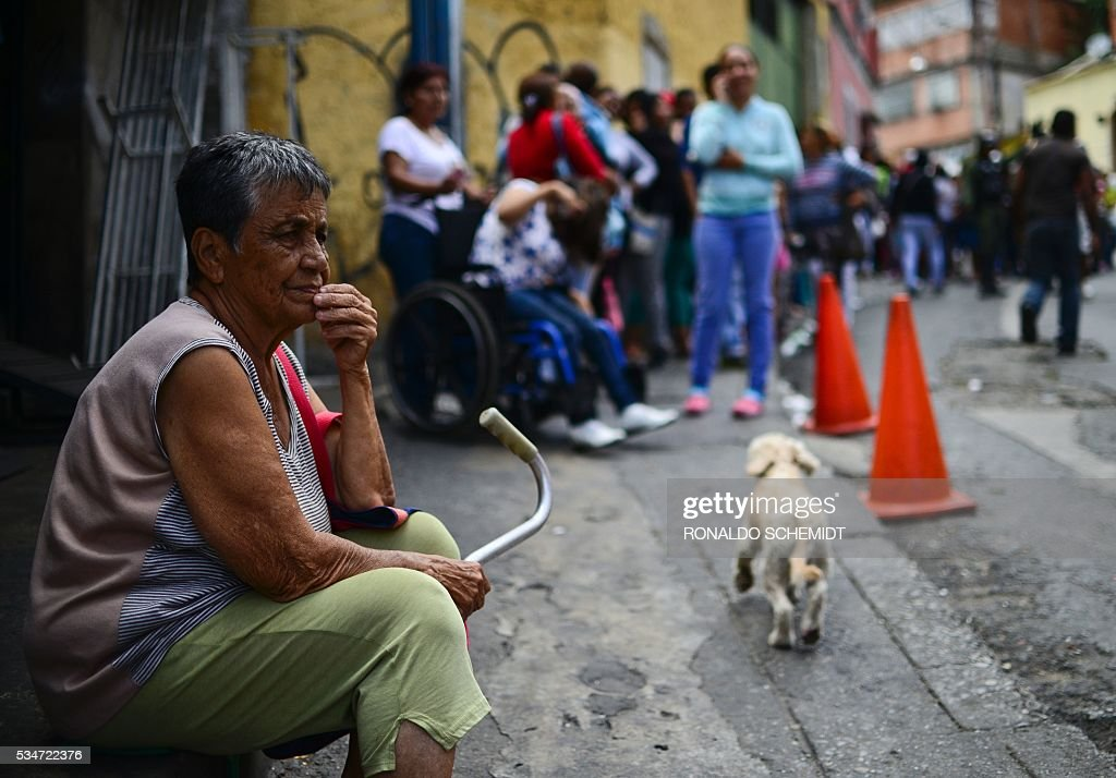 An elderly woman lines up to buy basic food and household items outside a supermarket in the poor neighborhood of Lidice, in Caracas, Venezuela on May 27, 2016. / AFP / RONALDO