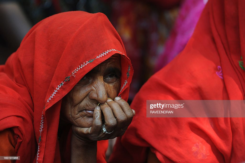 An elderly woman listens to speeches during a protest attended by activists from the National Federation of Indian Women, Aganwadi Teachers, All India Network of Sex Workers, and farmers, against the Congress-led UPA government as they demand entitlement for universal old age pension in New Delhi on March 6, 2013. More than 100 social organisations from across the country gathered in the capital to form a 'pension parishad', seeking addressal of universal pension for elderly people.