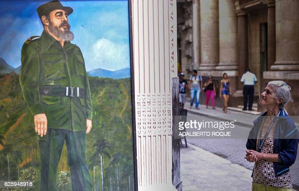 TOPSHOT An elderly woman looks at a mural depicting Cuban revolutionary leader Fidel Castro in a street of Havana on November 26 the day after he...