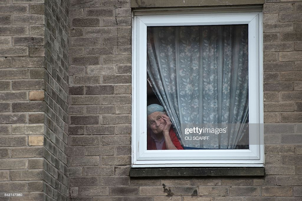 An elderly woman looks out from an upper floor window in the border town of Berwick-upon-Tweed in northern England close to the border between England and Scotland on June 26, 2016. Scotland's First Minister Nicola Sturgeon campaigned strongly for Britain to remain in the EU, but the vote to leave has given the Scottish National Party leader a fresh shot at securing independence. Sturgeon predicted more than a year ago that a British vote to leave the alliance would give pro-European Scots cause to hold a second referendum on breaking with the UK. SCARFF