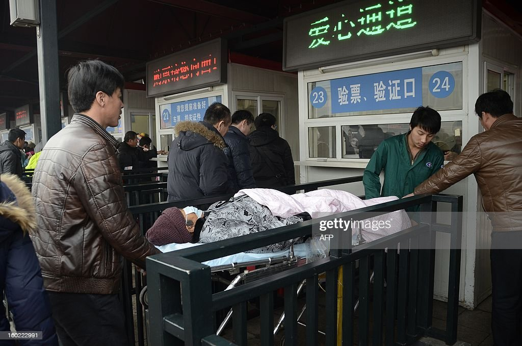 An elderly woman lying on a stretcher prepares to take a train at the entrance of the Beijing railway station on January 28, 2013. The world's largest annual migration began on January 26 in China with tens of thousands in the capital boarding trains to journey home for next month's Lunar New Year celebrations. AFP PHOTO / WANG ZHAO