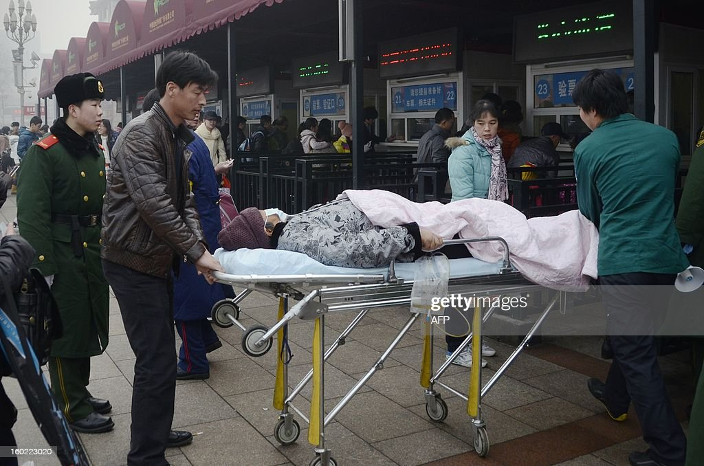 An elderly woman lying on a stretcher prepares to take a train at the entrance of the Beijing railway station on January 28, 2013. The world's largest annual migration began on January 26 in China with tens of thousands in the capital boarding trains to journey home for next month's Lunar New Year celebrations.
