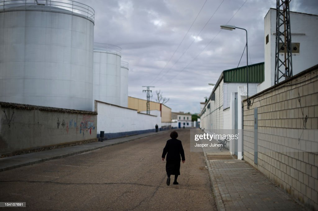 An elderly woman makes her way home past a door factory on October 12, 2012 in the small industrial town of Villacanas, Spain. During the boom years, where in its peak Spain built some 800,000 houses a year, more than Britain, Germany and France combined, and millions of wooden doors where needed, the people of Villacanas were part of a proud elite enjoying high wages and permanent jobs. Almost all of those doors used came from this small industrial town in the La Mancha province, some seven million a year, leaving with truck loads at the same time, from the now empty and silent Villacanas industrial park. With Spain in recession and the housing bubble busted, the door industry is shattered and unemployment in Villacanas, zero for nearly a generation, is rising fast.