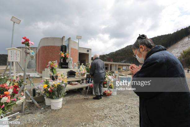 An elderly woman offers a prayer at Okawa Elementary School on the three year anniversary of the earthquake and tsunami on March 11 2014 in...