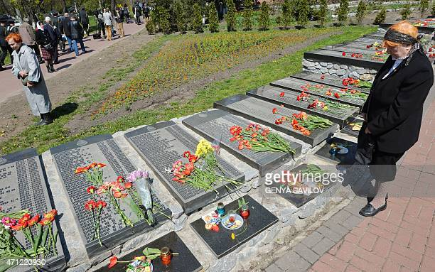 An elderly woman pays her respects to the victims of Chernobyl nuclear disaster at a memorial in the Ukrainian capital of Kiev on April 26 2015...
