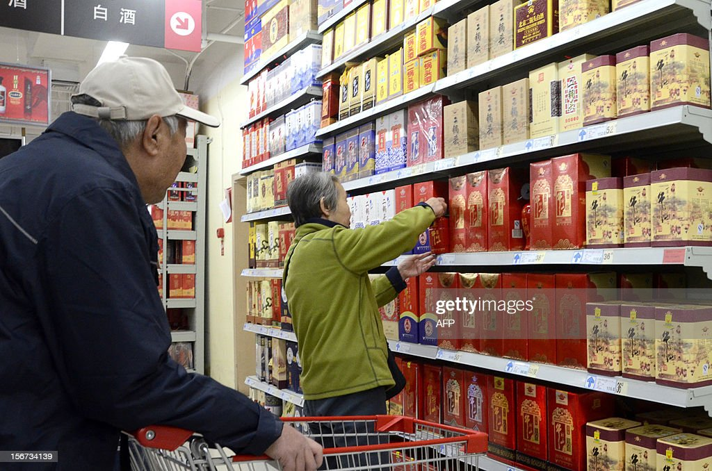 An elderly woman picks a bottle of white spirit from a shelve in a supermarket in Beijing on November 20, 2012. China Alcoholic Drinks Association said all Chinese 'White spirit' had plasticizer.
