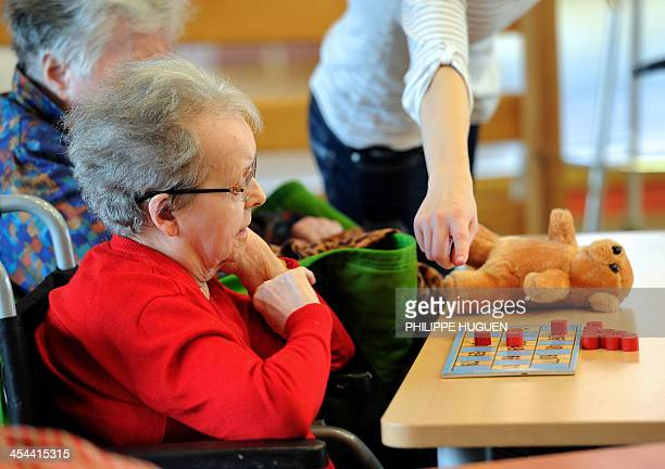 An elderly woman plays bingo at the Centre Montgre an EHPAD in Lens northern France on December 4 2013 AFP PHOTO / PHILIPPE HUGUEN