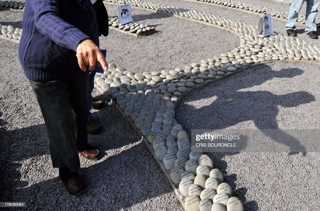 An elderly woman points at a symbolic graveyard of stones reading names of victims of the war against terrorist groups as The Shinning Path and the Tupac Amarus during the 80's and 90's, in Lima on August 28, 2013. Relatives of victims commemorate the 10th anniversary of the release of the report of the Commission of Truth and Reconciliation of Peru, which concluded that there were 69.000 people killed or missing during the 80's and 90's.