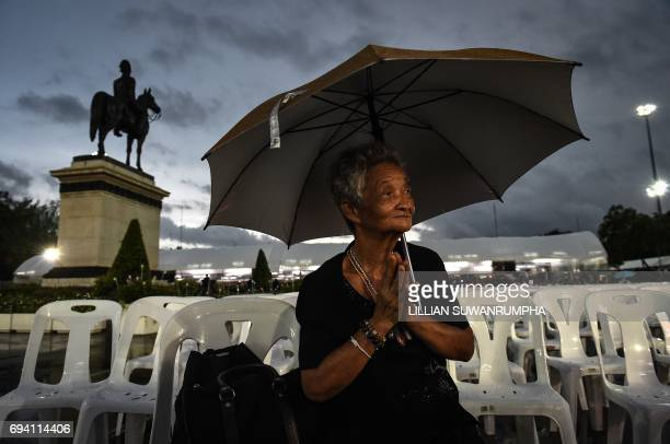 An elderly woman prays during a Buddhist ceremony for the late Thai King Bhumibol Adulyadej at the King Rama V Monument in Bangkok on June 9 2017 /...