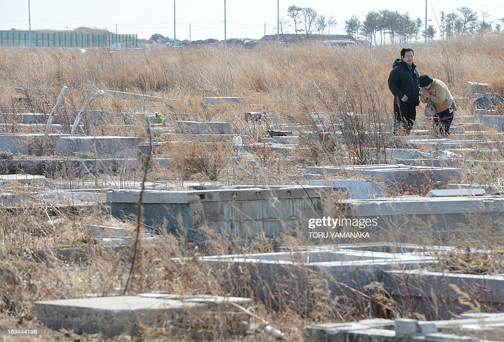 An elderly woman (R) prays in front of their family's grave at the desolate cemetery of the tsunami-hit Tozenji temple at Yuriage district in Natori, Miyagi Prefecture, on March 10, 2013, one day before the second anniversary of the March 11 earthquake and tsunami disaster. Japan will commemorate the second anniversary of a 9.0 magnitude offshore earthquake and giant tsunami that killed 15,880 people and left 2,694 unaccounted for, mainly in the Pacific coastline of the tohoku region in the nation's northeast. AFP PHOTO/Toru YAMANAKA