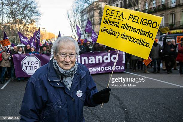 An elderly woman protesting during a demonstration against CETA carrying a placard that reads 'CETA danger work food climate democracy'