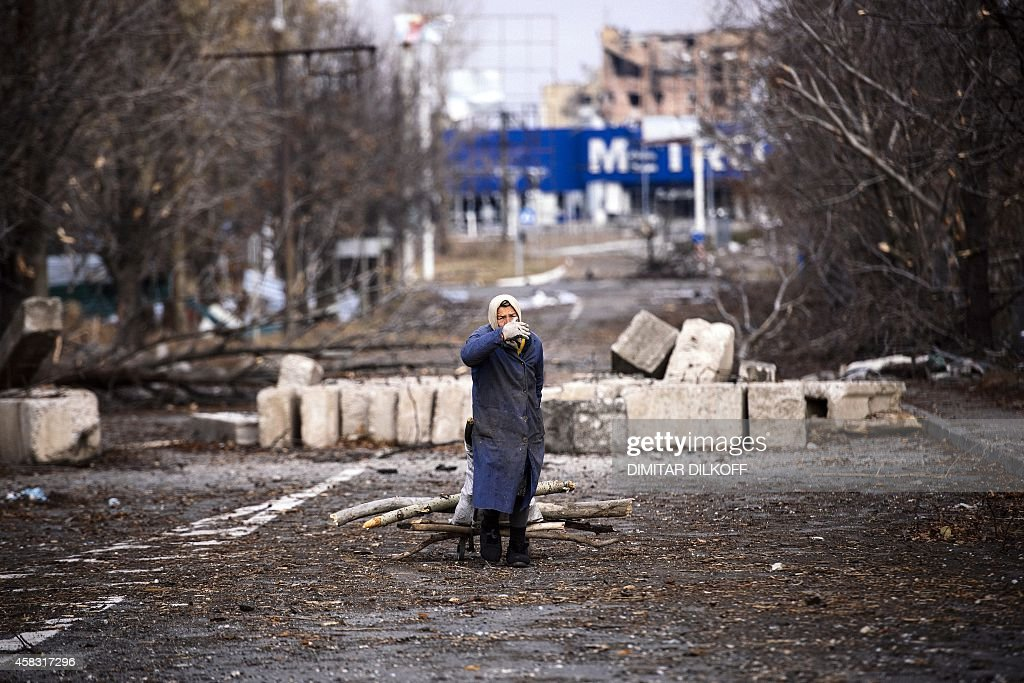 An elderly woman pulls cart with firewood near the Donetsk airport in eastern Ukraine on November 3 2014 EU foreign policy chiefs blasted Moscow's...