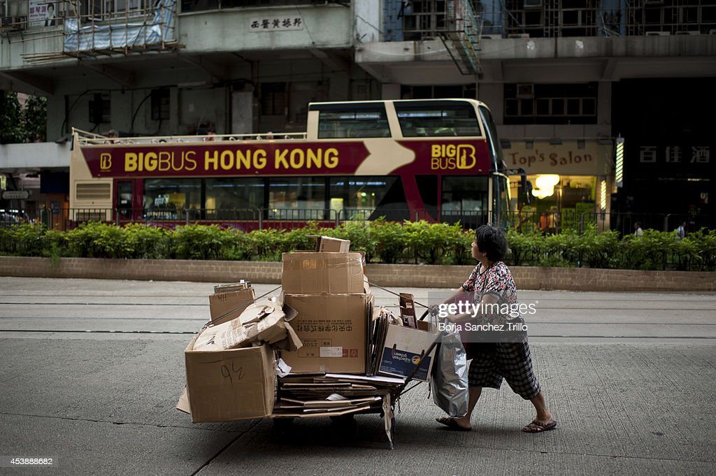 An elderly woman pushes a cart though a street on August 19, 2014 in Hong Kong, Hong Kong. A government-commissioned study headed by University of Hong Kong academic Nelson Chow Wing-sun proposed to fund HK $3,000 a month pension for every Hongkonger over 65, rich or poor, without a means test. The pension should be funded partly by contributions ranging from 1 to 2.5 per cent of employees' salaries, paid by employers and workers. One in three old people in Hong Kong lives below estimated poverty line some of them struggling to make a living collecting cardboard boxes and plastic bottles on the street.