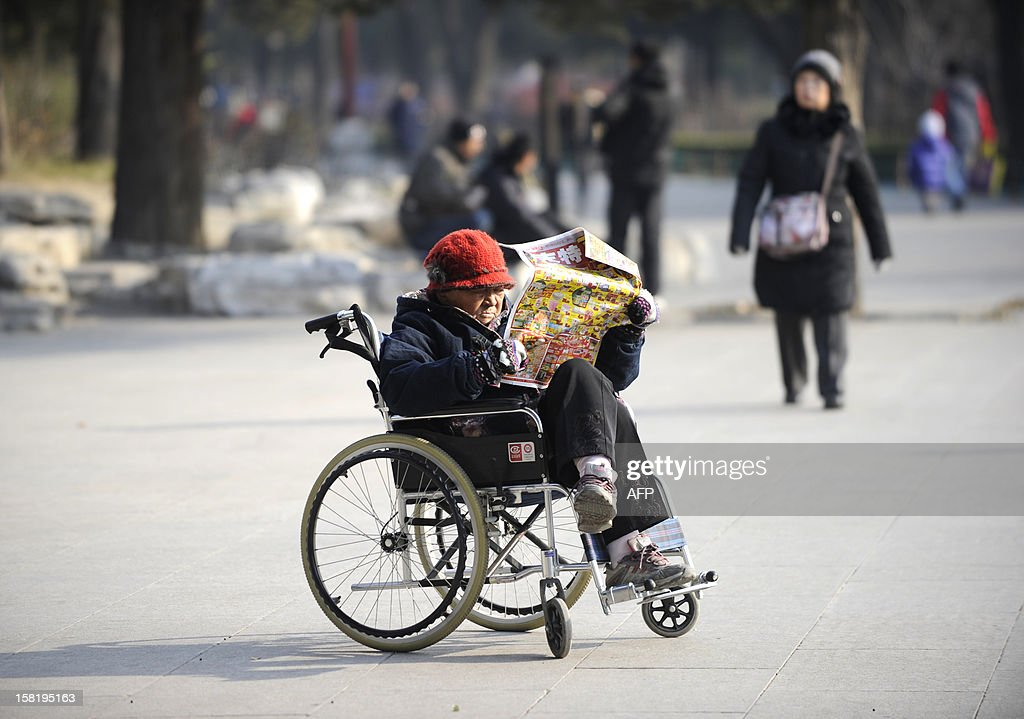 An elderly woman reads a supermarket brochure at a park in Beijing on December 11,2012. China's elderly face increasing uncertainty three decades since the one-child policy took hold, with no real social safety net, the law has left four grandparents and two parents with one caretaker for old age -- and bereaved families with none.