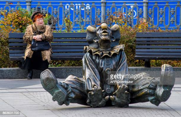 TOPSHOT An elderly woman rests on a bench next to a sculpture of a clown outside Nikulin Moscow Circus in Moscow on October 20 2017 / AFP PHOTO /...