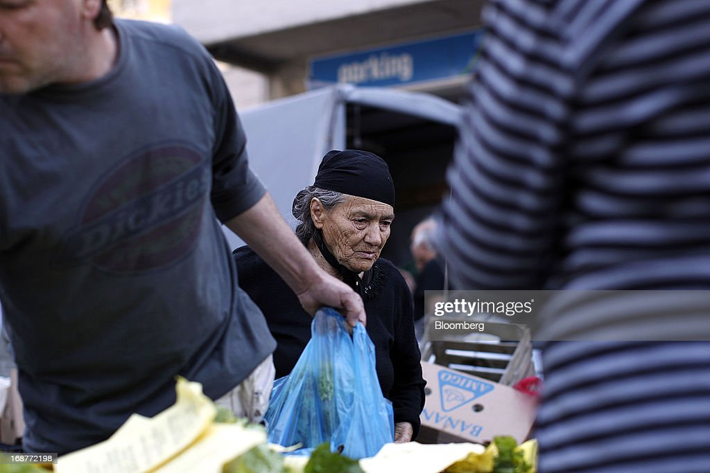 An elderly woman searches for free vegetables from a stall during a handout of leftover food by striking street vendors in Athens, Greece, on Wednesday, May 15, 2013. Greece's plans to return to international bond markets next year reflect the government's confidence it can draw a line under the country's debt crisis although the cost of borrowing suggests that might be premature. Photographer: Kostas Tsironis/Bloomberg via Getty Images