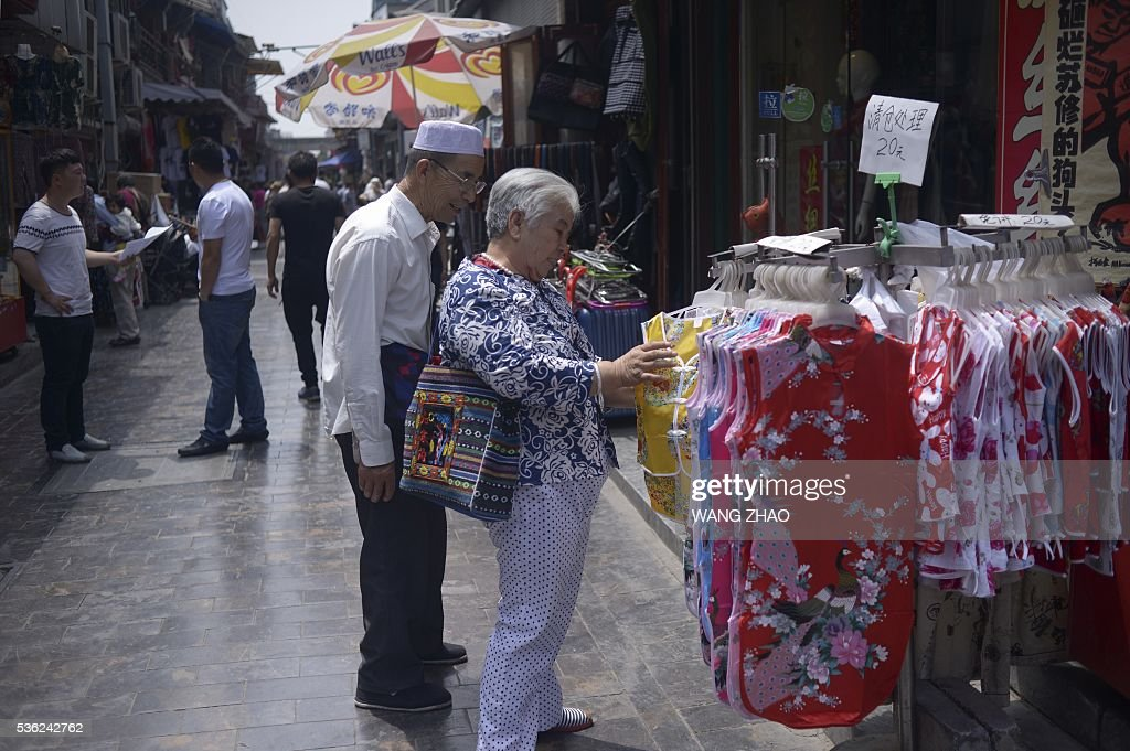An elderly woman selects cloth at a stall in Beijing on June 1, 2016. Activity in Chinese factories expanded for the third straight month in May, official data showed, a further sign of stabilisation in the world's second largest economy.The official Purchasing Manager's Index (PMI), which tracks activities in the country's factories and workshops, came in at 50.1 on June 1, according to the National Bureau of Statistics (NBS). / AFP / WANG