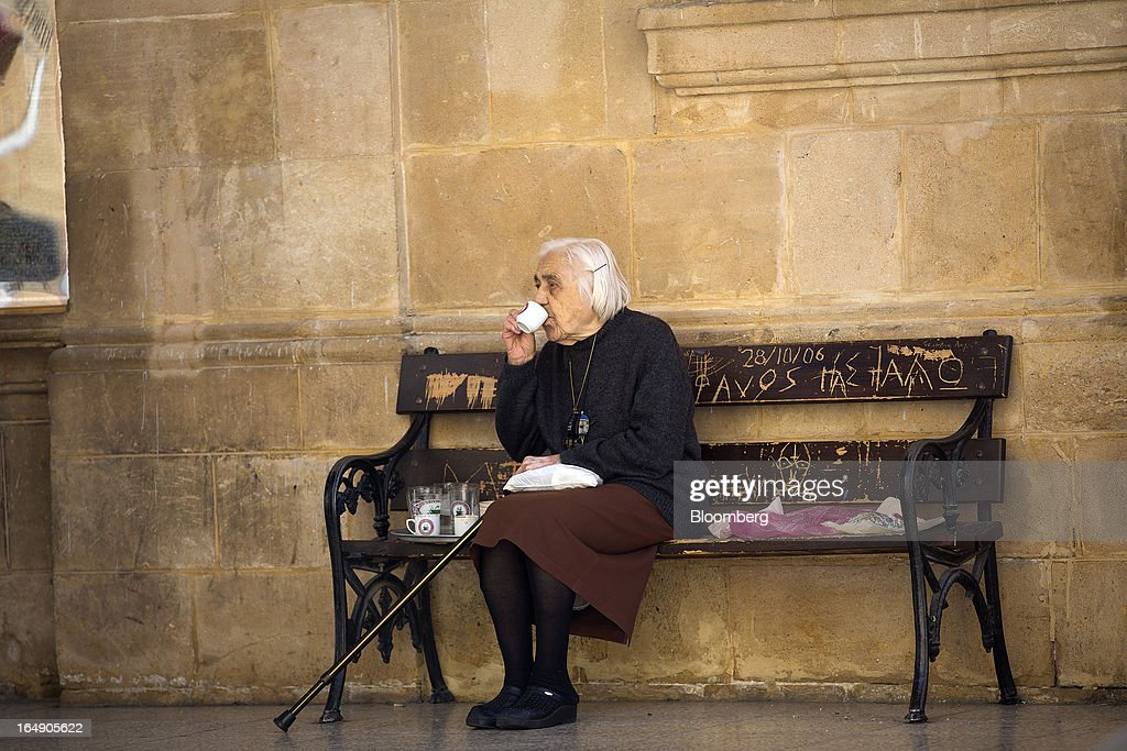 An elderly woman sits and drinks coffee on a bench in a churchyard in Nicosia, Cyprus, on Friday, March 29, 2013. Cypriots face a second day of bank controls over their use of the euro as officials in Europe urged the country to move quickly to lift the restrictions, the first time they have been imposed on the common currency. Photographer: Simon Dawson/Bloomberg via Getty Images
