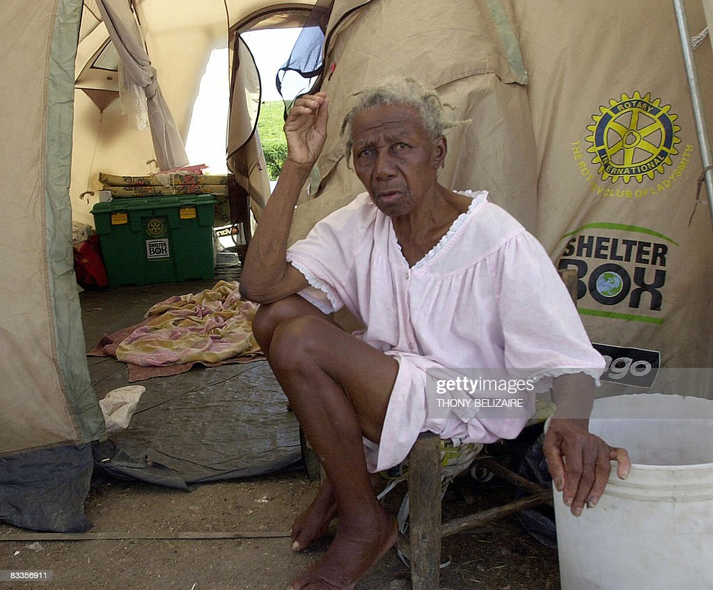 An elderly woman sits by a tent in a makeshift camp on October 17, 2008 in the village of Cabaret, 35km north of Port-au-Prince, where some 700 people, mostly women and girls, have taken refuge after their homes were destroyed by hurricane Ike in September. AFP PHOTO/Thony BELIZAIRE