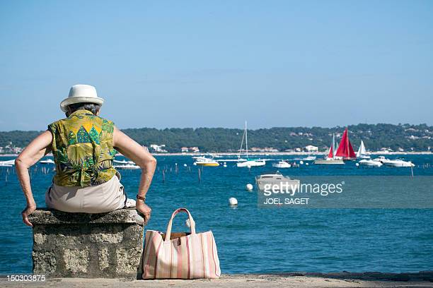 An elderly woman sits in front of the sea on August 14 2012 in LegeCapFerret southwestern France AFP PHOTO/JOEL SAGET