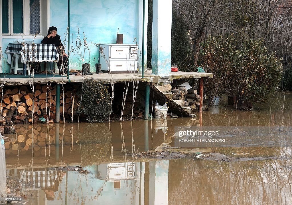 An elderly woman sits on a verandah in front of their flooded house in the village of Monospitovo near the town of Strumica on February 28, 2013. The torrential rains which from Sunday until Tuesday poured down on the fertile Strumica Valley inundated fields and villages, destroying or damaging crops and households. Tens of people in the region are now sheltered, as their homes were gravely damaged. Other parts in Eastern Macedonia had their share of flooding in the first half of the week, which took one victim.