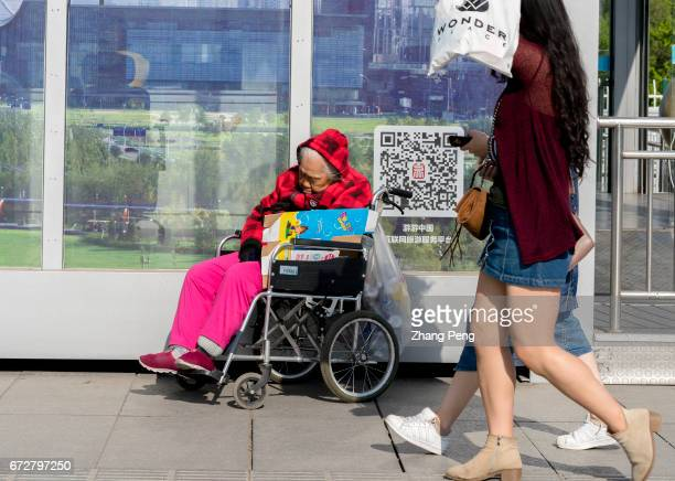 An elderly woman sits on her wheelchair resting at roadside Statistics show that China's 60yearold population has reached more than 230 million...