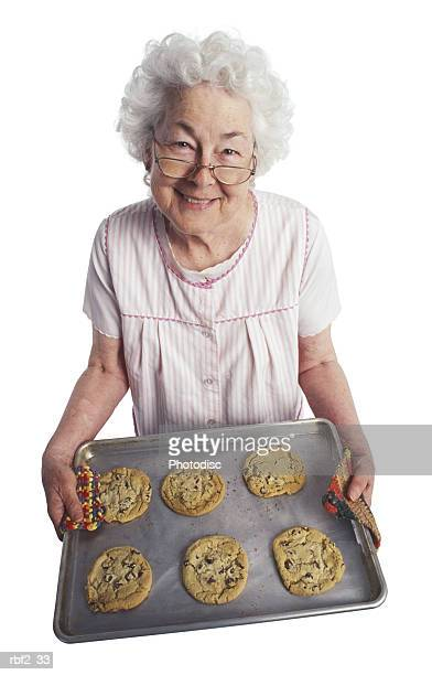 an elderly woman smiles up at the camera as she hold a tray of cookies