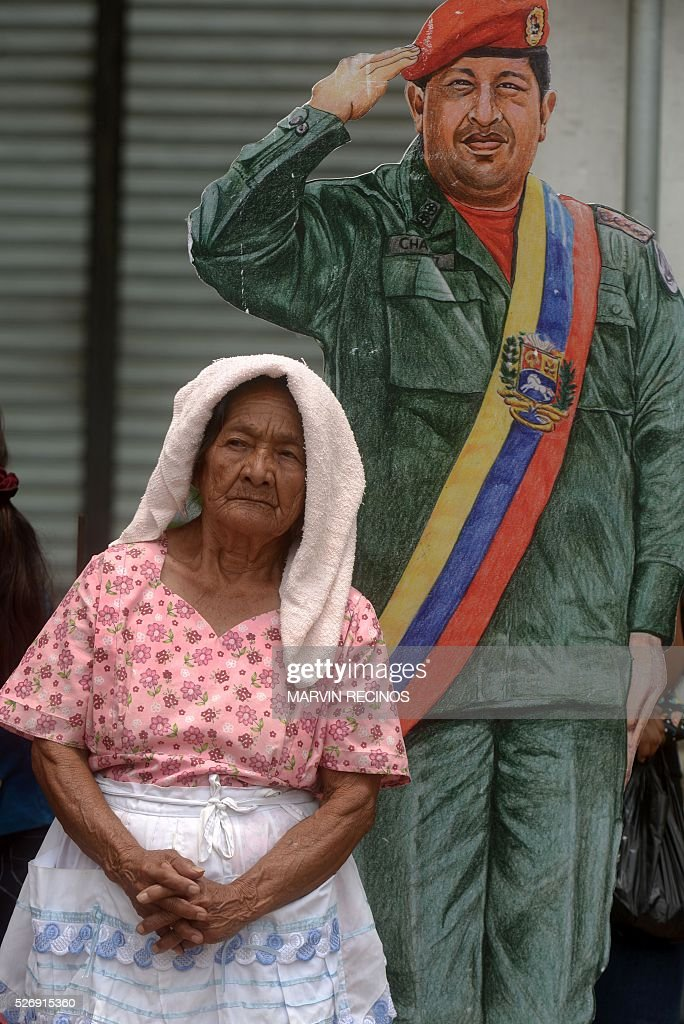 An elderly woman stands next to a poster of late Venezuelan president Hugo Chavez during a march to mark International Workers' Day, in San Salvador, on May 1, 2016. / AFP / Marvin RECINOS