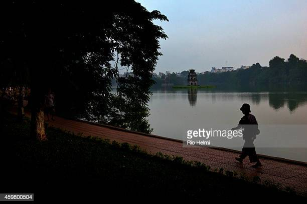 An elderly woman taking exercise walking around Hoan Kiem Lake in Hanoi wearing an old Vietnamese military helmet
