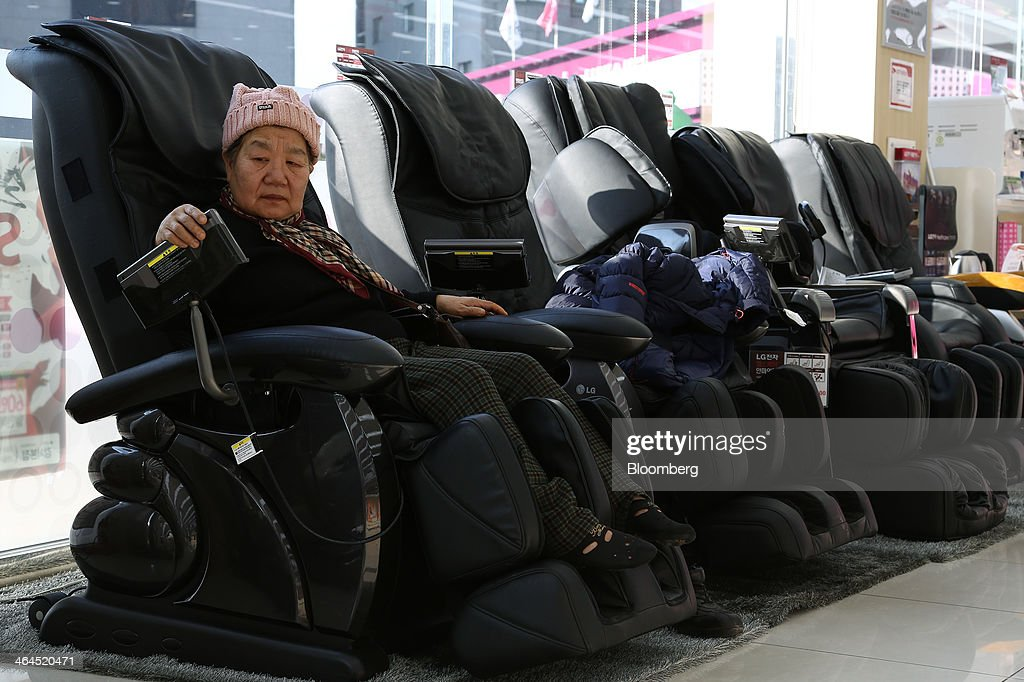 An elderly woman tries out an LG Electronics Inc. massage chair at the company's Bestshop store in Seoul, South Korea, on Wednesday, Jan. 22, 2014. LG Electronics, the worlds second-largest seller of televisions, is scheduled to announce fourth-quarter earnings on Jan. 27. Photographer: SeongJoon Cho/Bloomberg via Getty Images