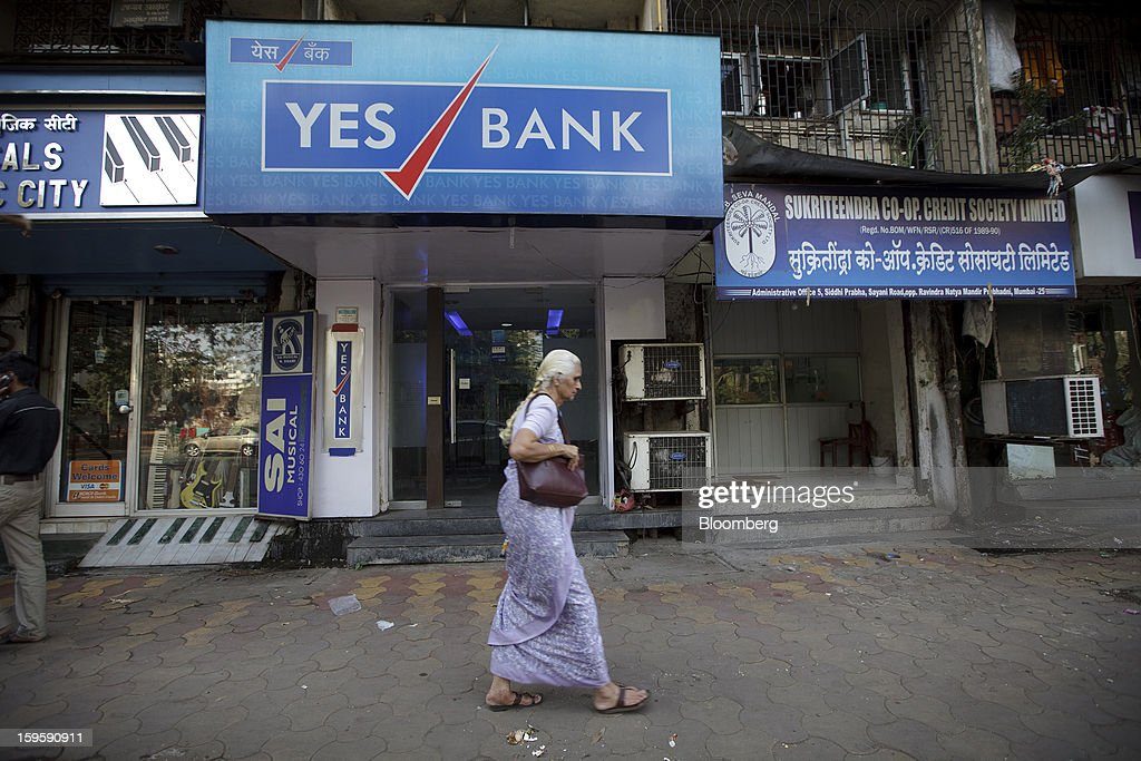 An elderly woman walks by a Yes Bank Ltd. automated teller machine (ATM) branch in Mumbai, India, on Wednesday, Jan. 16, 2013. India's financial system has been made vulnerable by a deterioration in bank assets and a lack of capital as the economy slowed, according to the International Monetary Fund. Photographer: Kuni Takahashi/Bloomberg via Getty Images