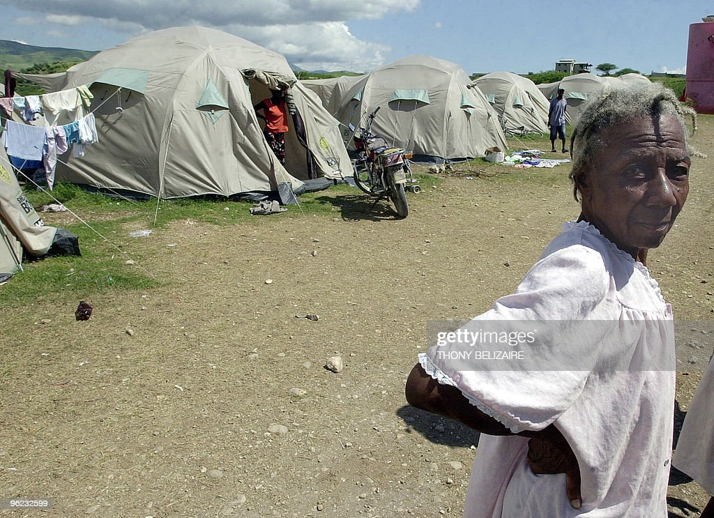 An elderly woman walks by tents in a makeshift camp on October 17, 2008 in the village of Cabaret, 35km north of Port-au-Prince, where some 700 people, mostly women and girls, have taken refuge after their homes were destroyed by hurricane Ike in September. AFP PHOTO/Thony BELIZAIRE