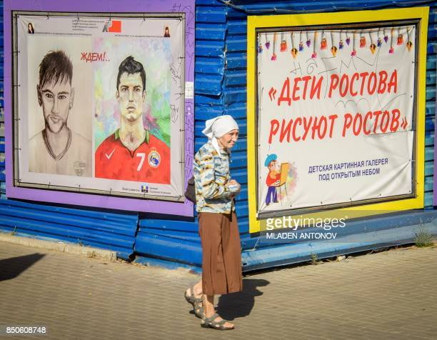 An elderly woman walks in front of a painting depicting football stars Christiano Ronaldo and Neymar in the southern Russian city of RostovonDon on...