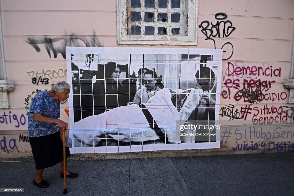 An elderly woman walks in front of a picture showing former Guatemalan dictator Jose Efrain Rios Montt on a trolley next to his daughter Zury Rios in...