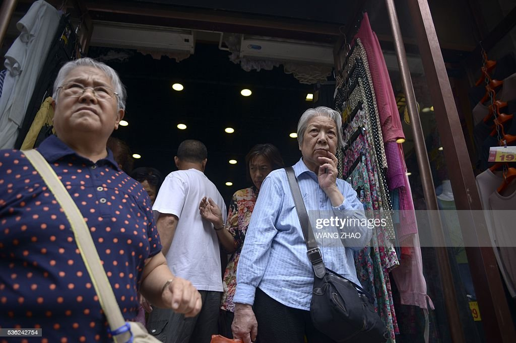 An elderly woman (R) walks out of a shop in Beijing on June 1, 2016. Activity in Chinese factories expanded for the third straight month in May, official data showed, a further sign of stabilisation in the world's second largest economy.The official Purchasing Manager's Index (PMI), which tracks activities in the country's factories and workshops, came in at 50.1 on June 1, according to the National Bureau of Statistics (NBS). / AFP / WANG