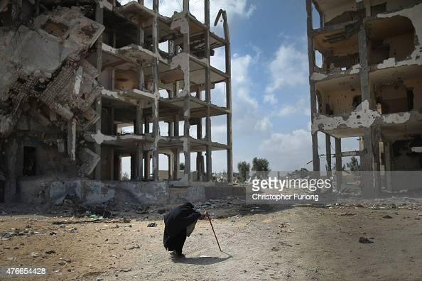 An elderly woman walks past bombed buildings that continue to scar the landscape of Gaza on June 10 Gaza City Gaza The devastation across Gaza can...