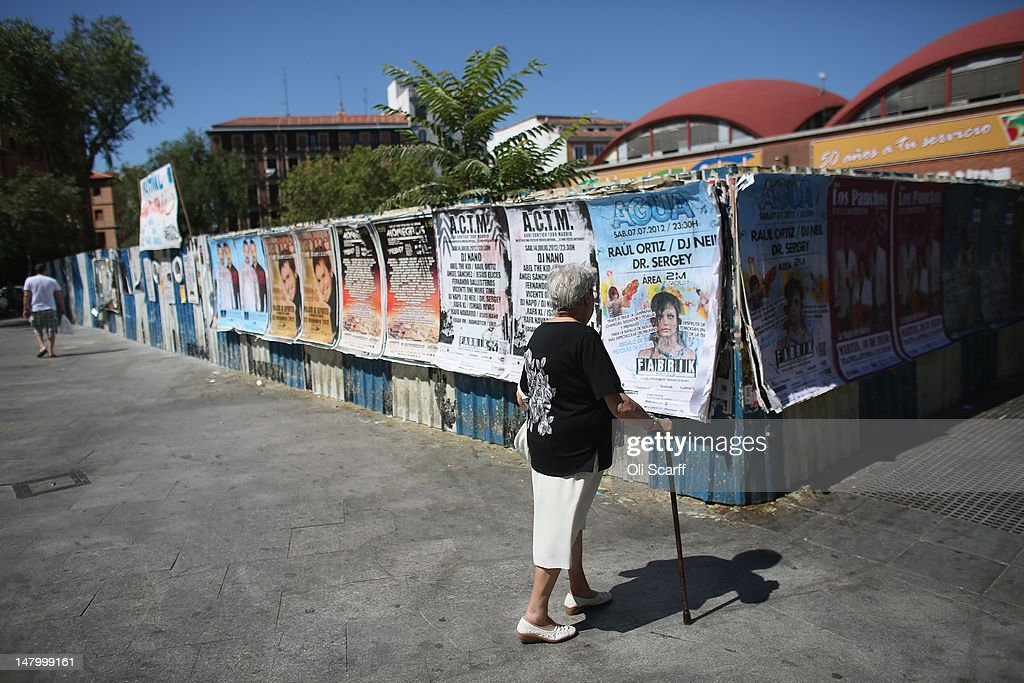 An elderly woman walks past fly posters near the Plaza de Cascorro on July 7, 2012 in Madrid, Spain. Despite having the fourth largest economy in the Eurozone, the economic situation in Spain remains troubled with their unemployment rate the highest of any Eurozone country. Spain is currently administering billions of euros of spending cuts and tax increases in a bid to manage its national debt. Spain also has access to loans of up to 100 billion euros from the European Financial Stability Facility which will be used to rescue the country's banks that have been badly affected by a crash in property prices.