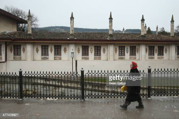 An elderly woman walks past the exterior of the Khan's Palace also called Hansaray in Crimea on March 9 2014 in Bakhchysarai Ukraine Bakhchysarai was...