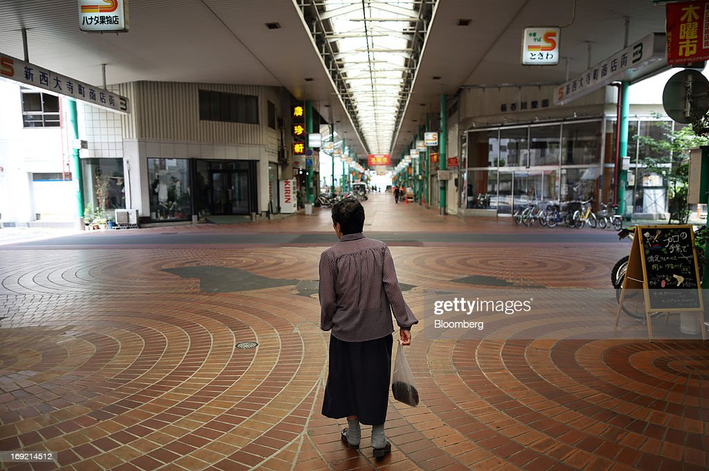 An elderly woman walks through a shopping street in Okayama, Japan, on Tuesday, May 21, 2013. The Bank of Japan, forecast to maintain plans for expanded monetary easing at a meeting ending on May 22, is targeting 2 percent inflation in two years after more than 10 years of entrenched deflation. Photographer: Tomohiro Ohsumi/Bloomberg via Getty Images
