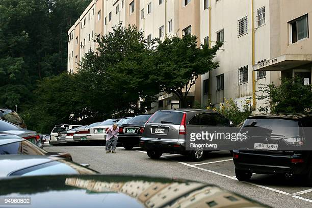 An elderly woman walks through the parking lot at the Gaepodong apartment complex in Seoul South Korea on Wednesday July 15 2009 South Korea's home...