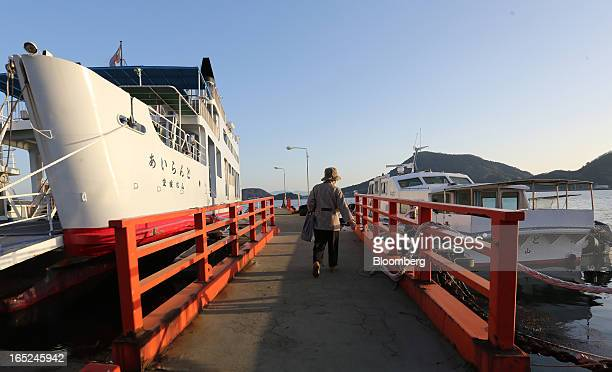 An elderly woman walks to board a ferry docked at Tomari port on Gogo Island in Matsuyama Ehime Prefecture Japan on Friday March 22 2013 A...