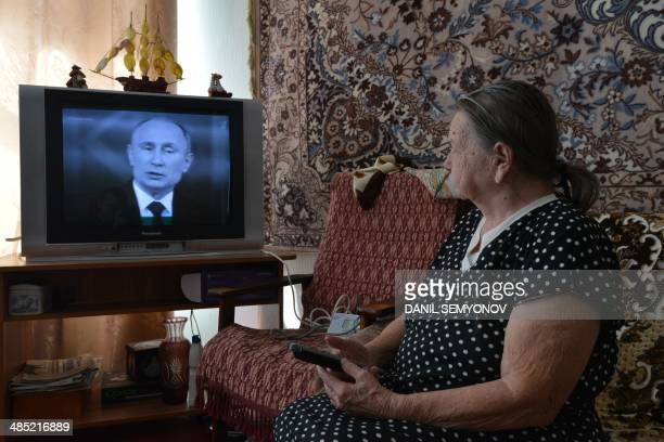 An elderly woman watches TV broadcasting of Russian President Vladimir Putin's annual televised questionandanswer session with the nation in the...