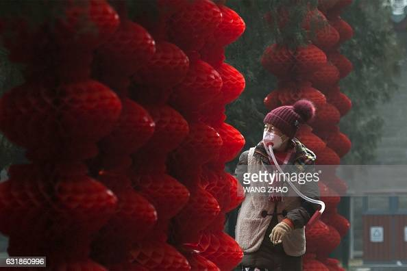 TOPSHOT An elderly woman wearing a homemade mask walks past lanterns hung ahead of the Lunar New Year at a park in Beijing on January 17 2017 The...