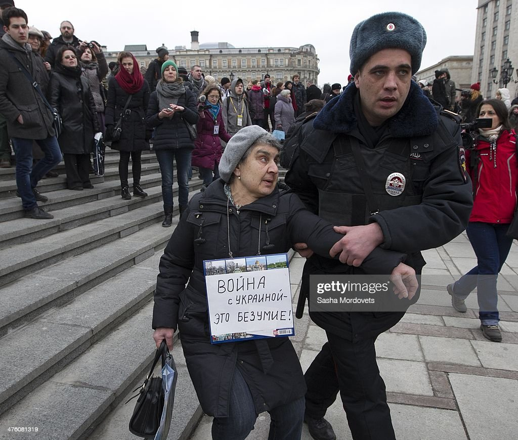An elderly woman wearing a sign that reads 'War against Ukraine is madness' is detained by riot police during an unsanctioned anti-war rally close to the Kremlin at Manezhnaya Square on March 2, 2014 in Moscow, Russia, Dozens of protesters were detained by police on Sunday during a rally against the military intervention in the Ukraine, after the parliament in Moscow gave President Vladimir Putin approval to use Russian military forces in Ukraine.