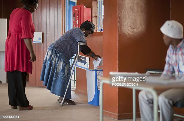 An elderly woman wearing traditional Xhosa beadwork and a dress with the image of former South African president Nelson Mandela votes on the second...